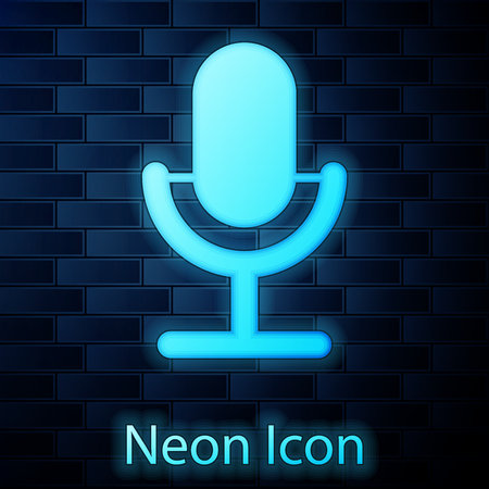Glowing neon Microphone icon isolated on brick wall background. On air radio mic microphone. Speaker sign. Vector Illustration