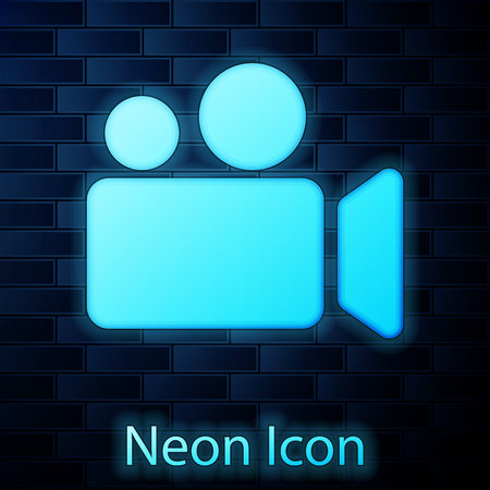 Glowing neon Movie or Video camera icon isolated on brick wall background. Cinema camera icon. Vector Illustration