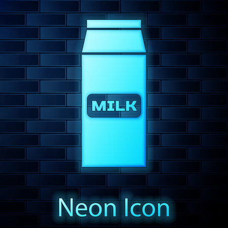 Glowing neon Paper package for milk icon isolated on brick wall background. Milk packet sign. Vector Illustration