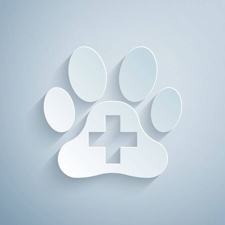 Paper cut Veterinary clinic symbol icon isolated on grey background. Cross hospital sign. A stylized paw print dog or cat. Pet First Aid sign. Paper art style. Vector Illustration