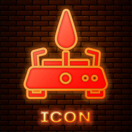 Glowing neon Camping gas stove icon isolated on brick wall background. Portable gas burner. Hiking, camping equipment. Vector