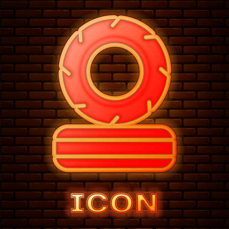 Glowing neon Lying burning tires icon isolated on brick wall background. Vector