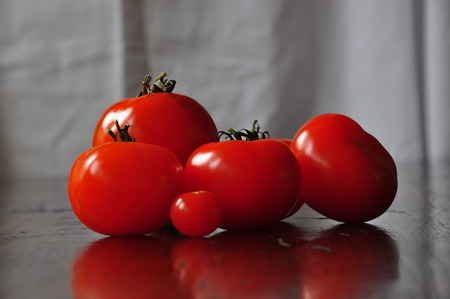 Tomatoes on a wooden table against a white background Stock Photo