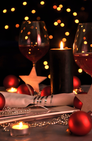 Christmas and New Year table setting with bokeh effect on black background