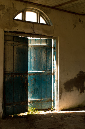 ajar: Old blue door is ajar, and through the slit pouring sunlight.