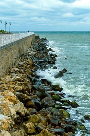 mare agitato: Rocks near the waterfront and rolls them sea waves. Archivio Fotografico
