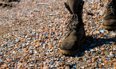 Male shoes close-up during a walk on the beach at small sea shells.