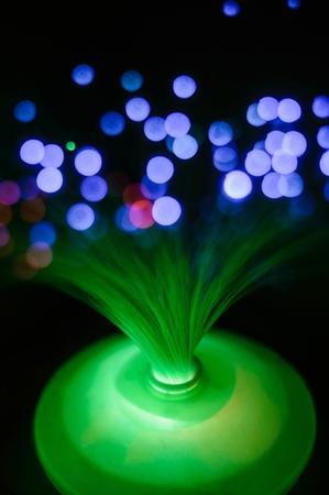 Green fiber-optic lamp-night light with a blue bokeh in the dark.