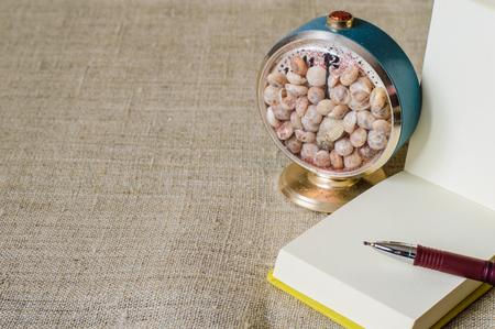 리넨 배경에 조개와 펜 및 공예 시계와 함께 열려있는 미니 메모장. 스톡 콘텐츠