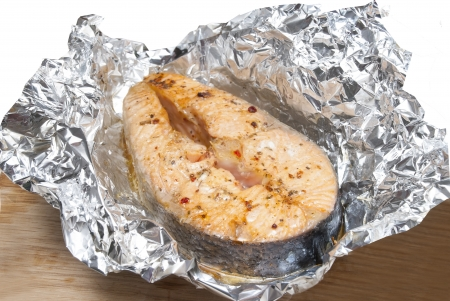 red fish with spice in foil on table photo