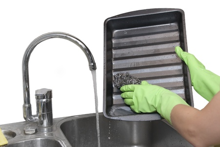 dripping pan: cleaning dripping pan with scraper Stock Photo