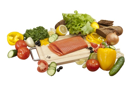 decomposed: red fish surrounded by vegetables. tomatoes, cucumbers, onions, peppers, parsley, lemon, salad, bread, lemon, olives Stock Photo