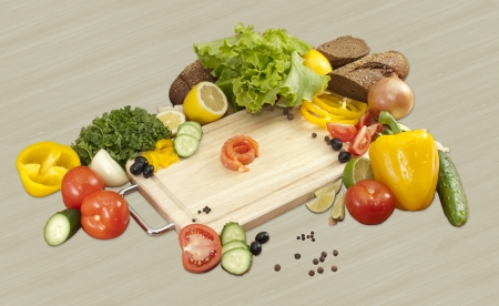 little piece of red fish surrounded by vegetables. tomatoes, cucumbers, onions, peppers, parsley, lemon, salad, bread, lemon, olives Stock Photo - 16500542