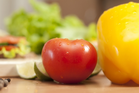 red tomato with waterdrops in the kitchen surrounded by vegetables Stock Photo - 16500669