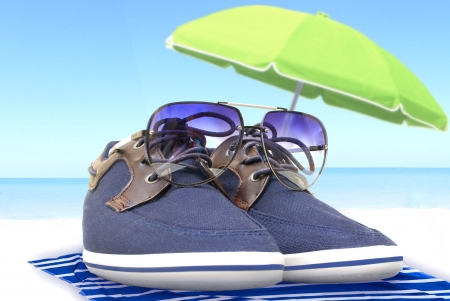 loafers: blue shoes with glasses resting on the shore under a parasol with a sea view