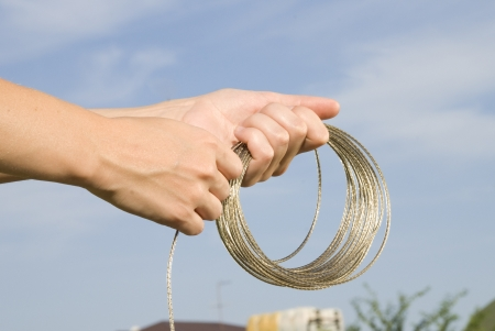 shiny rope in hands on sky background Stock Photo - 16563361