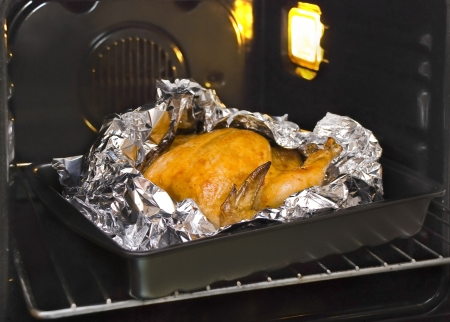 cooking juicy golden chicken in oven and foil Stock Photo - 16588281