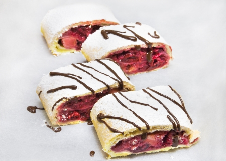 many cake rolls with strawberry jam and chocolate Stock Photo