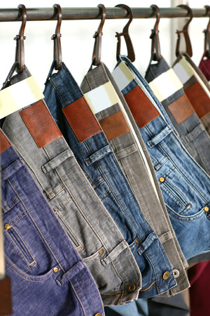 many colored fashion jeans sale in store Stock Photo