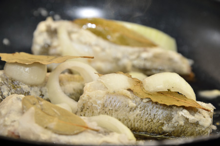 bay leaf: hake fish with onion and bay leaf on pan