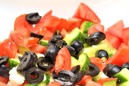 zoomed: salad with black  olives, red tomato and green cucumber
