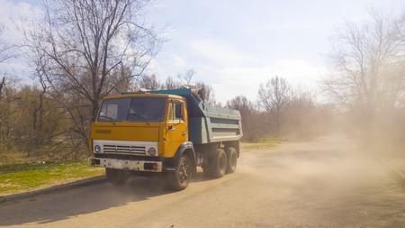 autotruck: yellow track remopve debris with dust