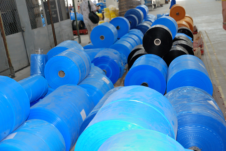 mercantile: many big  rolls of blue polyethylene in wharehouse Editorial