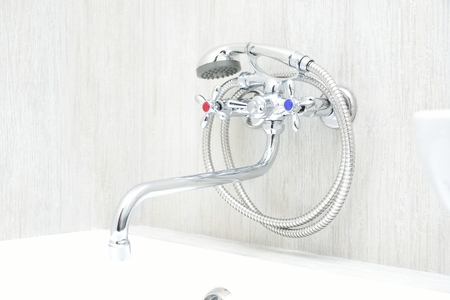 chrome faucet in bathroom with separate taps and showerhead