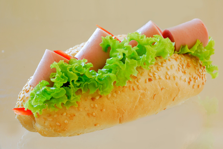 filled roll: submarine sandwich with sausage and green lettuce on glass table
