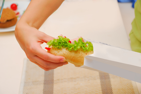 hoagie: hands pack up submarine sandwich in paper bag at kitchen