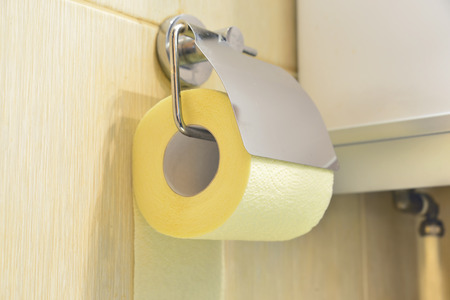 fecal: Toilet yellow paper and toilet paper holder. Stock Photo