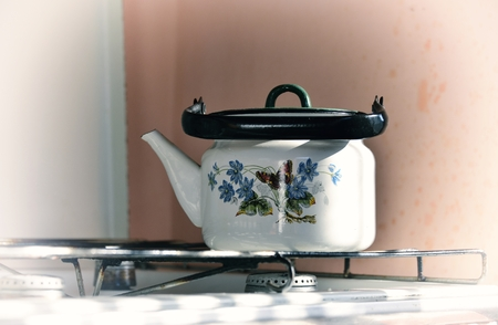 old gas stove: old white kettle with painting on a gas stove