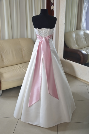 strapless dress: ivory wedding dress with pink bow and corset (choice of dress for the bride in the store ) Stock Photo