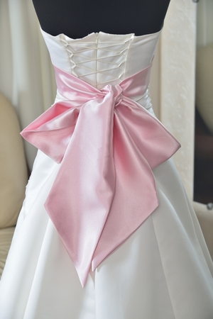 ivory wedding dress with pink bow and corset (choice of dress for the bride in the store ) Stock Photo