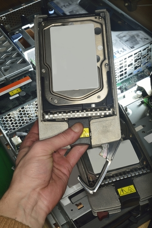 raid: hand showing hard disk (HDD) from server extracted from RAID Stock Photo