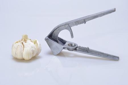 Garlic press (garlic crusher) with bulb of garlic