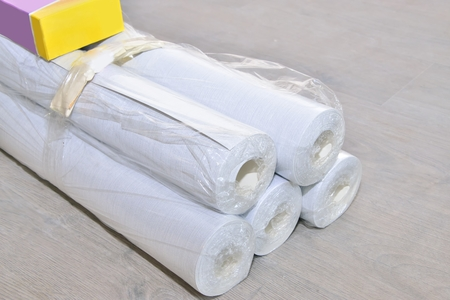 Wallpapering (unpacking rolls of wallpaper and glue from the store) Reklamní fotografie