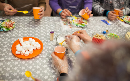 hands with spoons and plastic cups making sweets on colorful plates