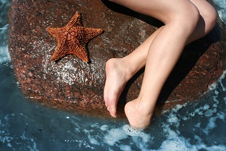 womans legs lying on a stone on the seacoast photo