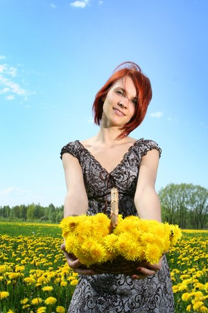 beautiful redhead girl with basket of dandelions photo