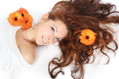 sch�ne junge M�dchen mit orangefarbenen Blumen im Haar