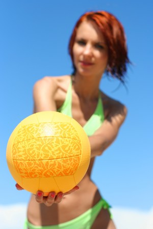 young girl playing with ball on the beach photo