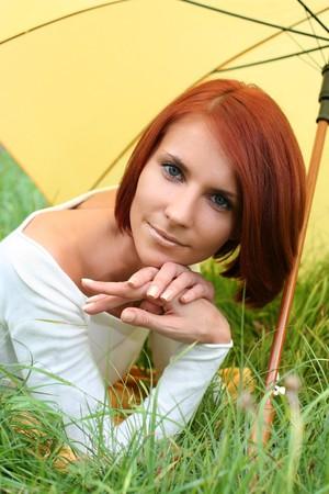 beautiful girl posing on grass under yellow umbrella photo