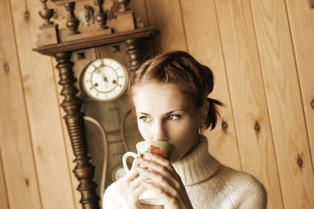 cute young girl drinking tea in cottage