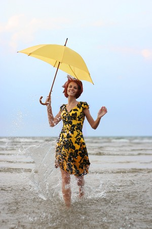 young girl in yellow dress running in the sea photo