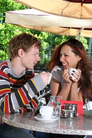 hombre tomando cafe: joven pareja de tomar café en la cafetería al aire libre Foto de archivo