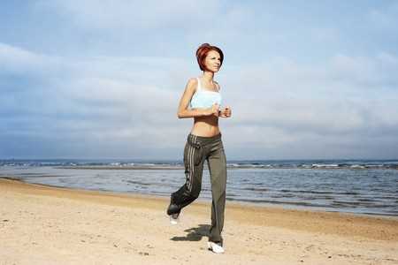young girl running on the beach Stock Photo