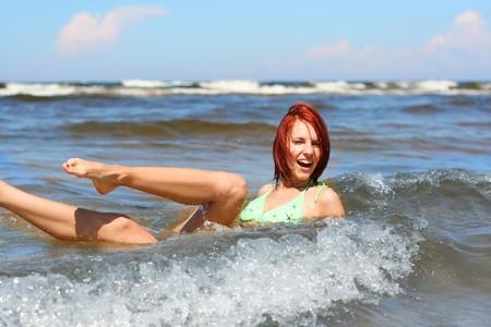 happy young girl having fun in the sea photo