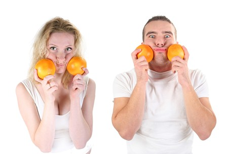 boy and girl playing with oranges in studio photo