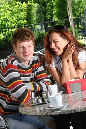 young couple drinking coffee in open-air cafe  photo